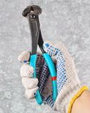 A man& x27;s hand with gloves holds metal nippers against a gray conc stock images