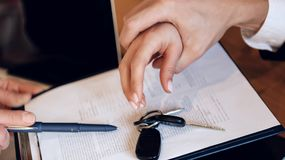 Man`s hand grabs woman`s hand, which tries to take car keys from table. Concept of property section under divorce. Property division concept Royalty Free Stock Photos