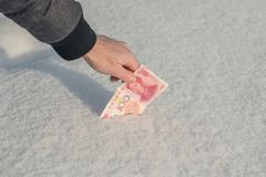 A man`s hand is getting a hundred chinese RMB from the snow.Concept. A man`s hand in a grey jacket is getting hundred chinese RMB from the snow. Close-up Stock Photography