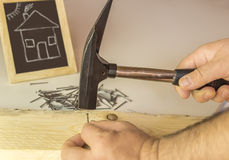 Man's hand hammering nail in wood Stock Photography