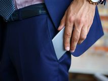 View of male hands touching mobile phone in a blue suit. Business concept. stock photo