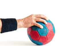 Man`s Hand on Handball. Man wearing a black sweatband holding a blue and red handball isolated on white Royalty Free Stock Photography