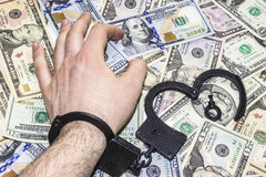 Man's hand is in handcuffs on background of dollars Royalty Free Stock Images