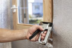 A man`s hand with the help of a construction stapler fastens ont. O a wooden beam a foil-insulated heater for the sauna, against the window. Close-up stock photos