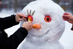 Man`s hand hold a big carrot, the nose of a real big snowman in wintere. Man`s hand hold a big carrot, the nose of a real big snowman in winter park, wintertime Stock Photography