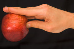 Man's hand holding an apple over dark background Royalty Free Stock Image