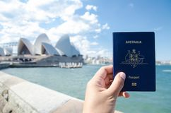 A man`s hand holding Australia passport with blurred background of Sydney Opera House for Concepts of traveling. SYDNEY, AUSTRALIA. – On December 14 stock photos