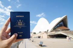 A man`s hand holding Australia passport with blurred background of Sydney Opera House for Concepts of traveling. SYDNEY, AUSTRALIA. – On December 14 stock photography
