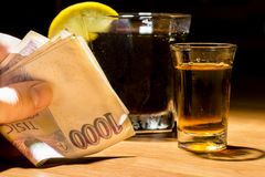 A man`s hand holding banknotes at a bar. Whiskey, cocktail and money at the bar. Alcoholic glasses and car keys. Do not drink alcohol while driving a car stock photography