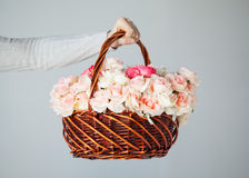 Man's hand holding basket full of flowers Stock Photos