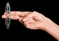 Man's hand holding a bike cog (chain ring). On the black background Stock Image
