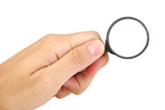 Man's hand, holding a black magnifying glass Stock Photo