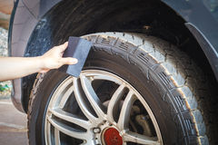 Man's hand holding a blue fabric cleaning car tires and wheels. In my home Royalty Free Stock Photo