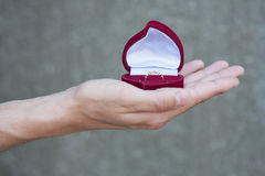 Man's hand holding a box with a church ring Royalty Free Stock Image