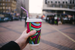 Man`s hand holding a bright color and a paper cup of coffee on the background of the city. Strong male hand holding a bright color and a paper cup of coffee on Royalty Free Stock Image