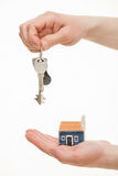 Man's hand holding a bunch of keys and a toy house. White background Stock Image