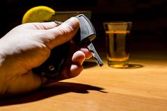A man`s hand holding car keys at a bar. Whiskey and cocktail at the bar. Alcoholic glasses and car keys. Do not drink alcohol while driving royalty free stock photos