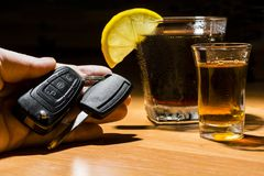 A man`s hand holding car keys at a bar. Whiskey, cocktail and money at the bar. Alcoholic glasses and car keys. Do not drink alcohol while driving royalty free stock photography