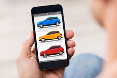 Person Holding Cellphone With Colorful Cars On Screen stock photo