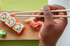 Man`s hand holding chopsticks and eating california sushi rolls on a wooden board stock image