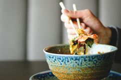 Free Man`s Hand Holding Chopsticks Over A Plate Of Japanese, Thai, Chinese Meal - Rice, Mushroom, Vegetables. Cafe Stock Photos - 102941353