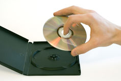 Man's hand holding a compact disc taken from a box Royalty Free Stock Image