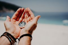 Man`s hand holding compass against the backdrop of beach and sea. The concept of travel, summer vacation, holiday and. Journey stock images