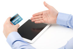 Man's hand holding a credit card over a tablet computer and the Stock Images