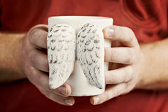 Man`s hand holding a cup of vintage shabby wings close-up.  Stock Images