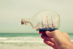 Man's hand holding decorative boat in the bottle in front of sea horizon. vintage filtered. Stock Photo