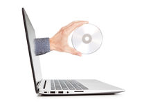 Man's hand holding a disk sticking out of the notebook. Royalty Free Stock Photography