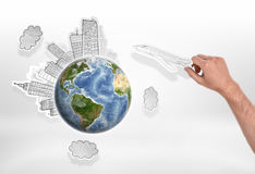 Man`s hand holding drawn airplane over globe with city sketches. Royalty Free Stock Images