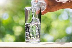 Man`s hand holding drinking water bottle water and pouring water into glass on wooden tabletop on blurred green bokeh background Stock Photo