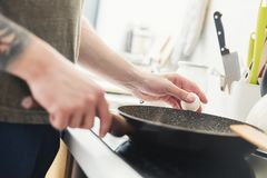 Man preparing fried eggs in the kitchen Stock Photography
