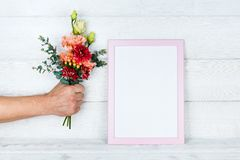 Man`s hand holding flowers and a photo frame on wooden background. Stock Photography