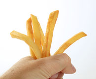 Man's hand holding French fries Stock Photography
