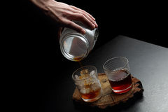 Man`s hand holding a galss jar. Hot and cold coffee pouring into two glasses Royalty Free Stock Photo