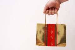 Man's hand holding a gift bag. Man's hold holding a gold gift bag next to white background Stock Images