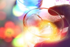 Man`s hand holding a glass of alcohol drink with ice cubes Royalty Free Stock Photography