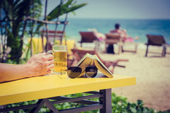 Mans hand holding a glass of beer in a beach cafe. Vacation the Stock Photos