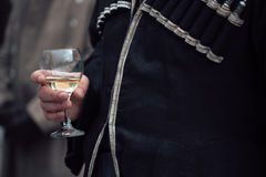 Man's hand holding a glass of champagne. A man in a historical costume Stock Photography