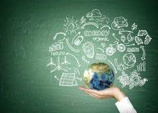 Man's hand holding globe against blackboard Royalty Free Stock Image