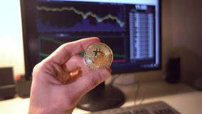 Man`s hand holding gold bitcoin on stock market chart bitcoin. Symbol of investment in cryptocurrency