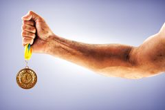 Man`s hand is holding gold medal on a blue background. Winner in a competition Royalty Free Stock Image