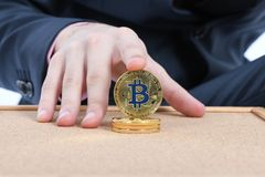 Man`s hand holding golden Bitcoin on brown textured cork background stock photos