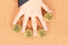Man`s hand holding golden Bitcoin on brown textured cork background royalty free stock photos