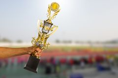 Man`s hand holding golden winner trophy cup on blurred sport stadium. With crowd background royalty free stock images