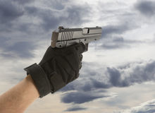 Man's hand holding gun Royalty Free Stock Photo