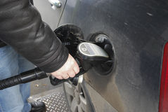 Man's hand holding a gun to the fueling of the car. Royalty Free Stock Image