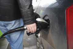 Man's hand holding a gun to the fueling of the car. Stock Image